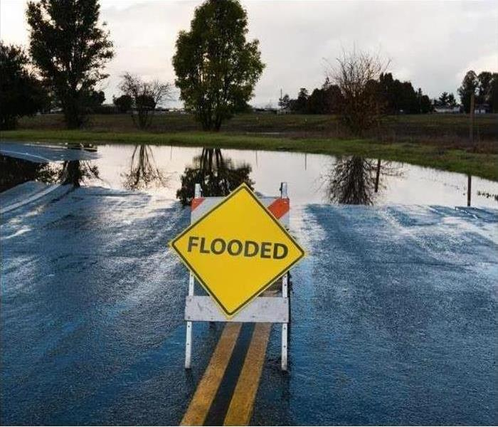 This is a sign that says flooded that is in the road to prevent people going into a flooded area